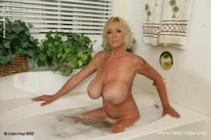Mature blonde soap up her giant breasts while taking a bath