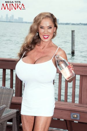 Mature pornstar Minka shows her massive breasts and rubs her clit outdoors