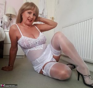 Smiley mature mom Lorna Blu offers her great big tits in white lace lingerie