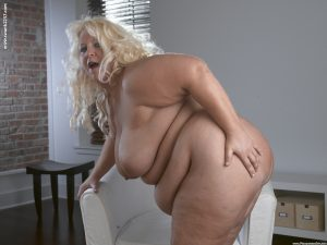 Older SSBBW with blonde hair removes white slip to model in the nude