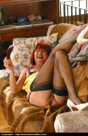 Aged redhead Miss Abigail pleasures herself on couch in black nylons