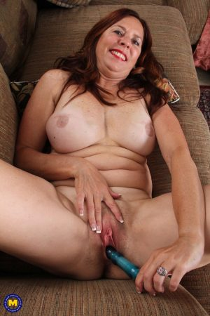 Mature wife Claire W removes her dress and plays with a sex toy in a solo