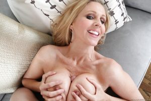 Saucy MILF gives a titjob and takes cum between her round boobs