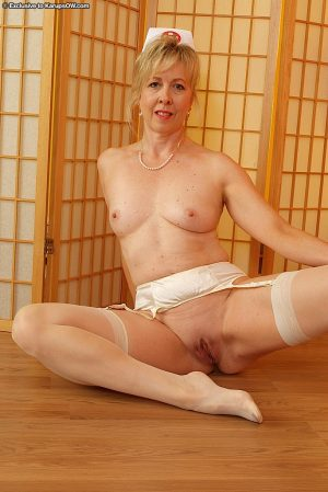 Sassy mature nurse in nylons taking off her uniform and spreading her legs