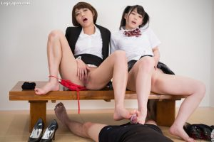 Japanese schoolgirls pet their pussies while giving a footjob
