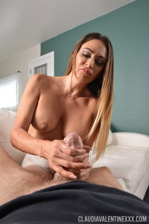 Busty female Claudia Valentine sports a camel toe while giving a handjob