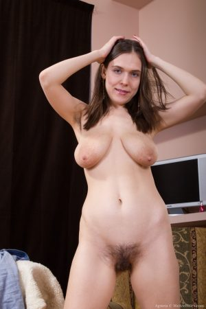 Lovely brunette with big tits Agneta exposes her hairy pussy on the sofa