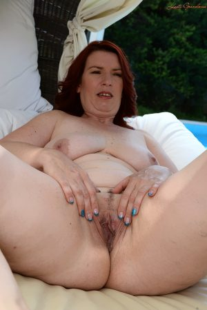 Mature redhead Viola lets out those naturals and poses on the outdoor bed
