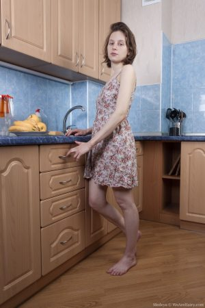Amateur girl Medeya shows her unshaven armpits and pussy in her kitchen