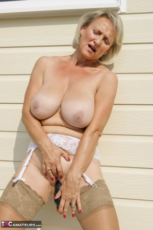 Mature amateur Sugar Babe uncups her large tits before masturbating on a patio