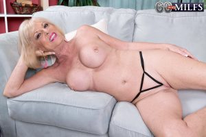 Blonde nan Scarlet Andrews plays with her pierced nipples after getting naked