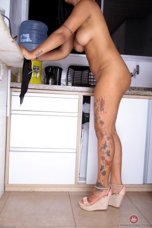 Sexy ebony female removes her thong to show her bald pussy in the kitchen