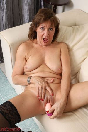 Mature lady Lynn uncovers her saggy tits before toying her bald pussy