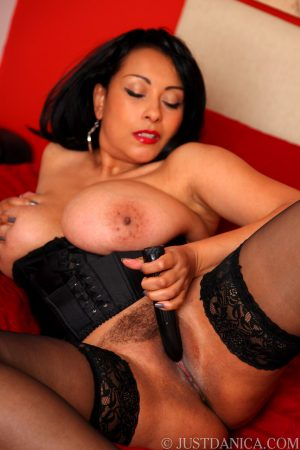 Curvaceous cougar in stockings Danica Collins plays with a black sex toy