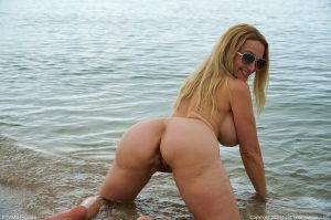 Blonde amateur Billi shows her enhanced tits and ass while naked at the beach