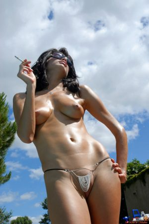 Glamour model Marie smokes outdoors in shades and a G-string