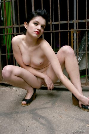 Young brunette Angelle strips on fire escape stairs and behind the building