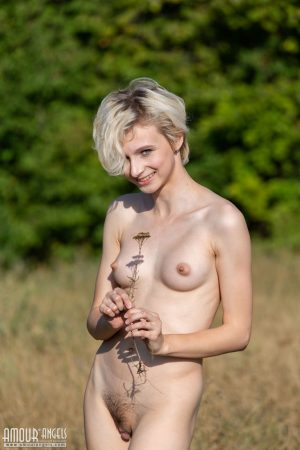 Nerdy female ditches her book and glasses before getting naked in a field