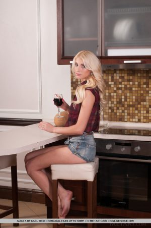 Sexy blonde teen Alma A doffs jean shorts and sleeveless shirt to model naked