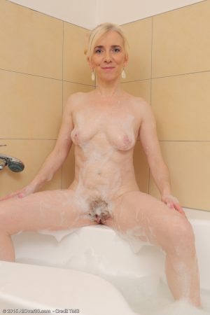 Slim older lady Dorena plays with her pussy during a bubble bath
