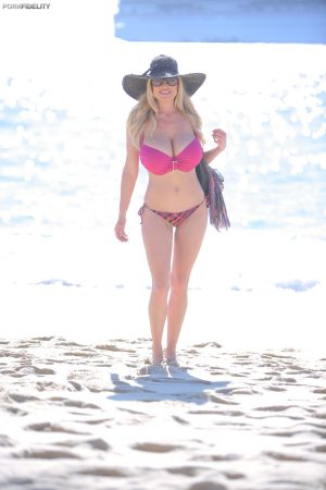 Buxom blonde babe in pink Kelly Madison flaunts her curves on the beach