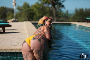 Busty fat tattooed model Galda Lou losing her yellow swimsuit at the pool