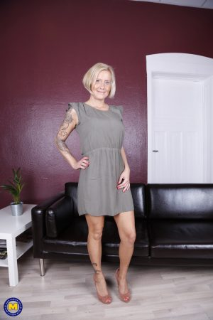 Attractive inked granny Leni shows her huge tits and masturbates with a toy