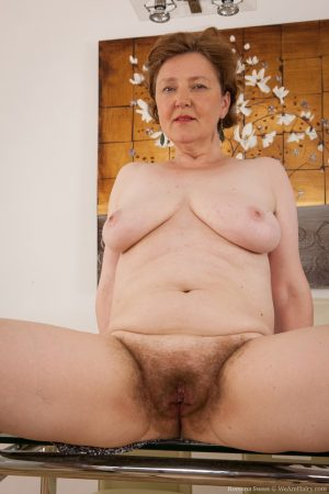 Busty lady Romana Sweet gets rid of her lace panties to show her hairy cunt