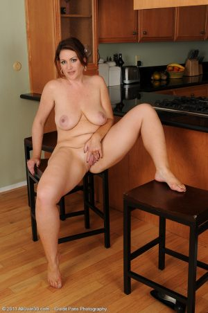 Hot chubby Ryan rests her natural big tits on the kitchen table & spreads nude