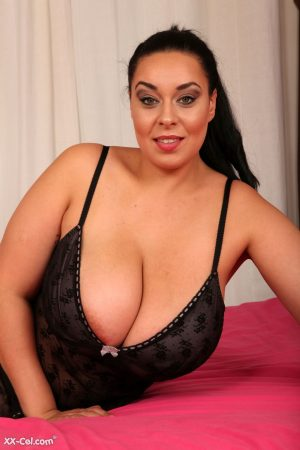British mom Anastasia Lux lets out her monster breasts and poses nude on a bed