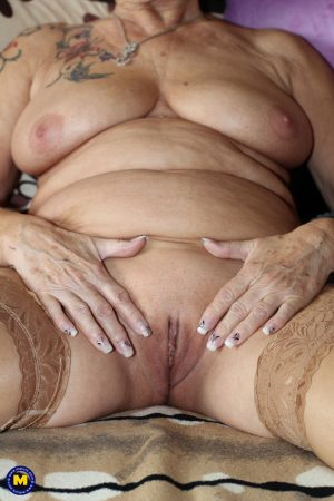 German granny Gerdi strips & spreads her sweet shaved old pussy on a bed