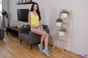 Little brunette Roxy Sky strips to her socks and fingers herself in a chair