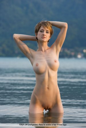 Outdoor girl Silke gets her firm big tits wet wading in the river naked