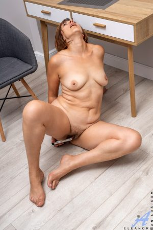 Mature redhead Eleanor disrobes at desk prior to dildoing her vagina