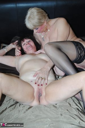 Mature lesbians get into a 69 position on top of bed sheets to eat pussy