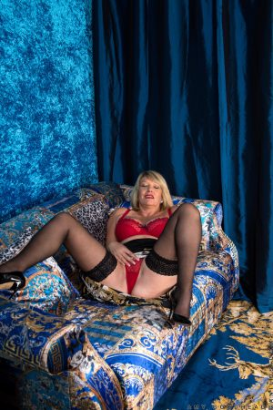 Mature British blonde Amy Goodhead removes her panties and fingers her holes