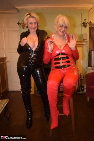 Mature lesbians get together in head-to-toe latex attire on a loveseat