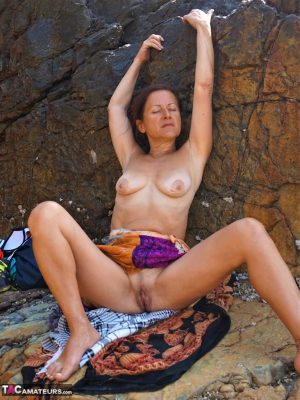 Mature amateur Diana Ananta shows her tan lined boobs and twat on rocky shelf
