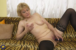 Mature Spanish woman in stockings Sandra G toying her hungry pussy on a sofa