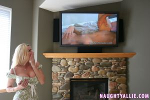 Busty blonde Naughty Allie jerks off her hubby while he watches adult videos