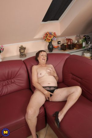 Short granny Eva S plays with her nipples and toys her fat pussy on the sofa
