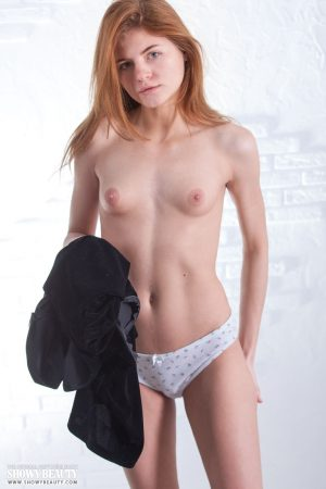 Young redhead Persik peels off her clothes to display her thin body