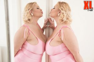 Blonde BBW Samantha holds her large breasts while licking a mirror