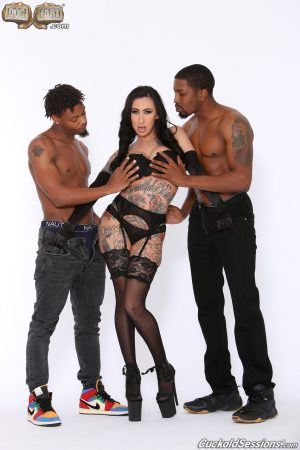 Inked cougar Lily Lane sucks two black dongs and takes them in her holes