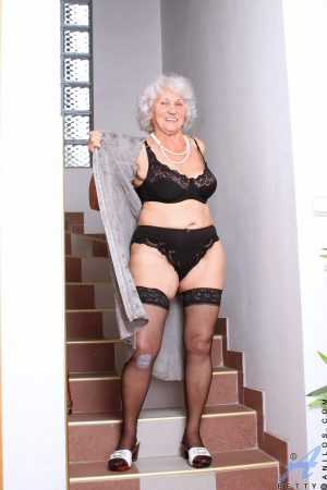 Cute granny Betty strips to her lingerie and masturbates on the stairs