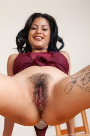 Petite brunette Daniela Flor flaunting her super hairy crotch on the table