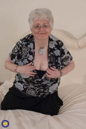 Kinky granny Caroline V fondles her big breasts & toys her fat pussy on a bed