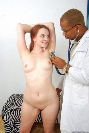 Natural redhead Andrea Sky strips before interracial sex with a doctor