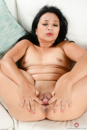 Asian mature Lucky Starr exposing her tasty shaved vagina on a couch
