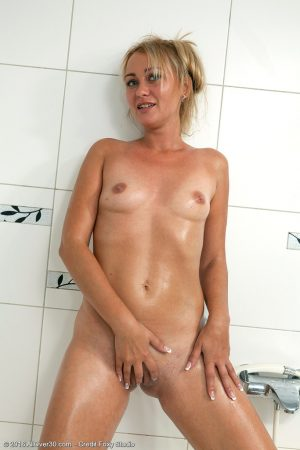 Over 30 blonde Nancy Acty soaps up her naked body while in the bathtub